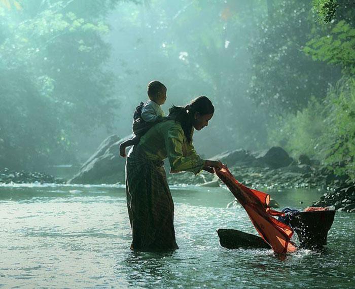 Wanita Bali Dengan Anak Di Sungai