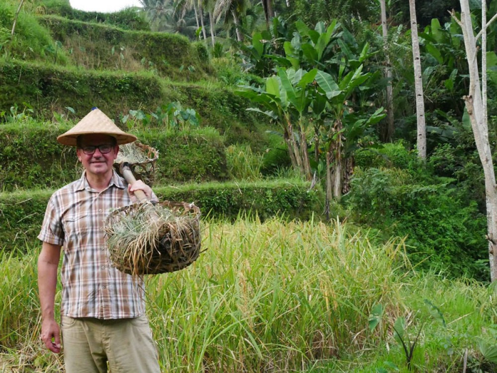 A Visitor Pose by Balinese Farmer Attribute at Tegalalang Rice Terrace